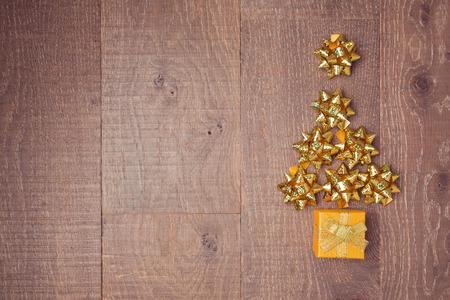 moños de navidad: Árboles de Navidad de arcos decorativos y cajas de regalo sobre fondo de madera. Vista desde arriba