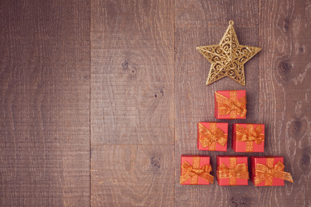 cajas navideñas: Christmas tree made from gift boxes in wooden background. View from above