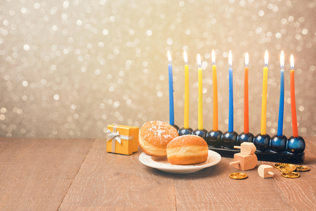 Jewish holiday Hanukkah celebration with menorah over bokeh background. Retro filter effect
