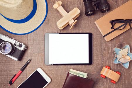 デジタル タブレットのモックアップとオブジェクトの旅行や休暇の概念の背景。上からの眺め