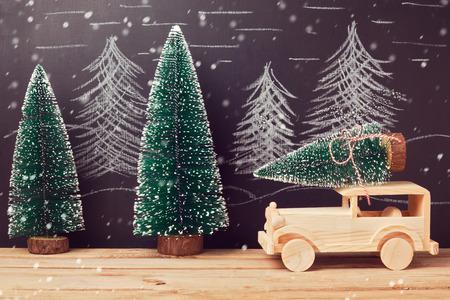 黒板の背景の上の木製のテーブルの上のおもちゃの車のクリスマス ツリーとクリスマスのお祝いコンセプト