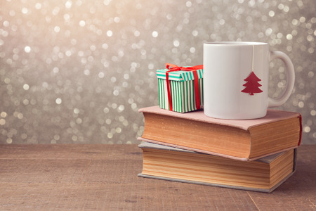 retro christmas tree: Christmas celebration with cup and gift box on books over bokeh background
