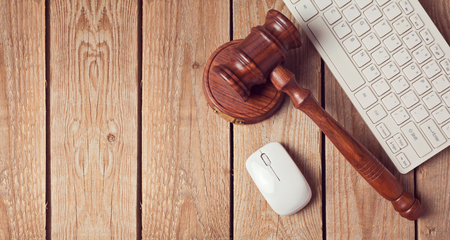 Law gavel and keyboard on wooden background. Online law enforcement concept. View from above Archivio Fotografico