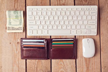 財布、お金および木製の背景上のキーボードでオンライン ショッピングのコンセプトです。上からの眺め