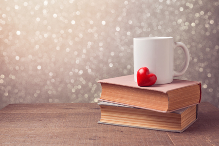 Valentine's day celebration with cup and heart on books