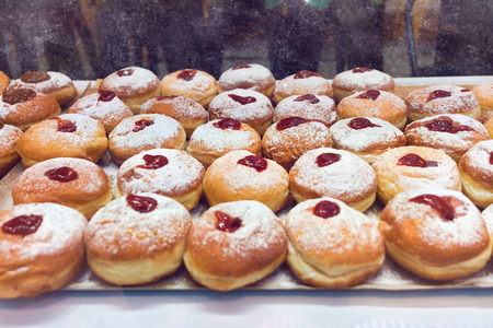 Doughnut sufganiyot for Hanukkah celebration in bakery shop Banco de Imagens