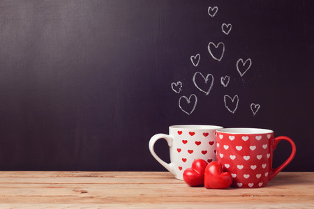 romantic love: Valentines day concept with hearts and cups over chalkboard background