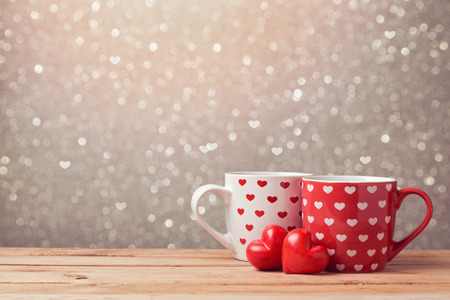 Valentine's day holiday celebration with hearts and cups over bokeh background Foto de archivo