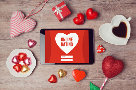 up view: Online dating cocept with digital tablet mock up and heart chocolates. Valentines day romantic celebration. View from above
