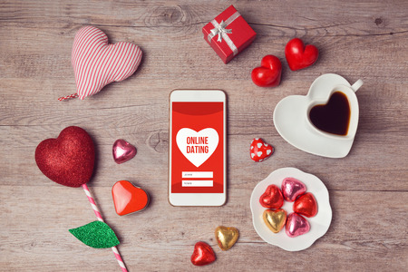 up view: Online dating cocept with smartphone mock up and heart chocolates. Valentines day romantic celebration. View from above Stock Photo