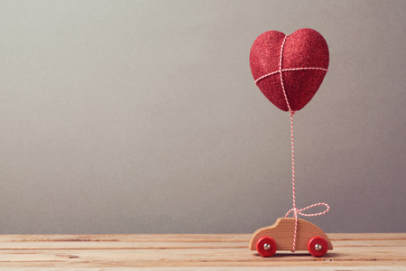 concept car: Heart shape balloon and car toy on wooden table. Valentines day concept.