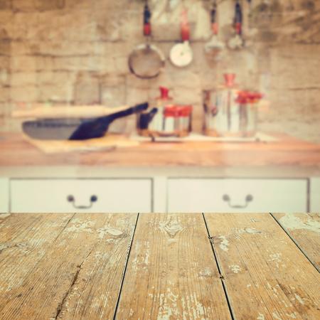 Empty wooden vintage table over kitchen blurred background Foto de archivo