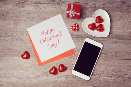 Valentine's day flat lay with note paper and smartphone. View from above