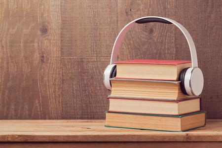 auriculares: concepto de libros de audio con la pila de libro viejo y los auriculares en mesa de madera Foto de archivo