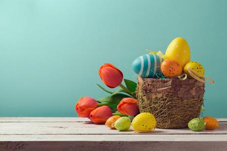 Easter egg decorations with flowers over blue background Standard-Bild