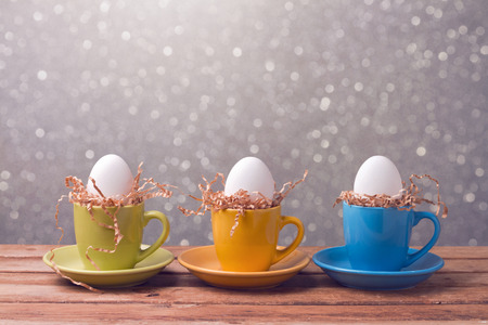 Easter holiday creative background with eggs in coffee cups