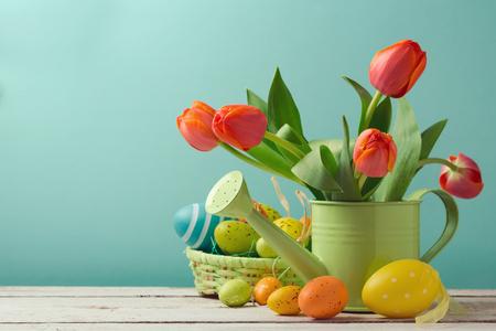 Festa di Pasqua con i fiori del tulipano e la merce nel carrello delle decorazioni dell'uovo Archivio Fotografico
