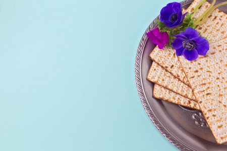 Passover background with matzah, seder plate and spring flower. Flat lay view from above