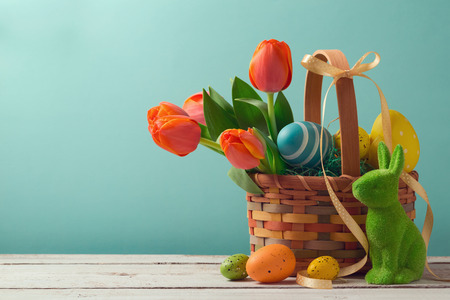 Easter holiday basket with eggs, flowers and easter bunny