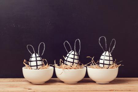 黒板にウサギの耳を持つモダンなイースターエッグの装飾です。創造的なイースターの背景。