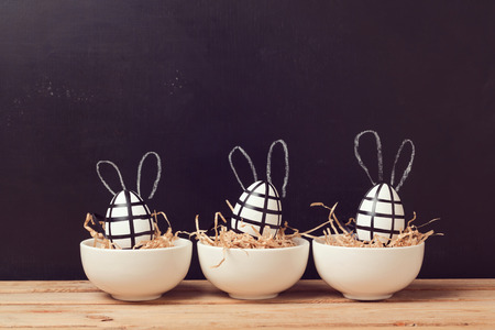Modern easter egg decorations with bunny ears on chalkboard. Creative easter background.