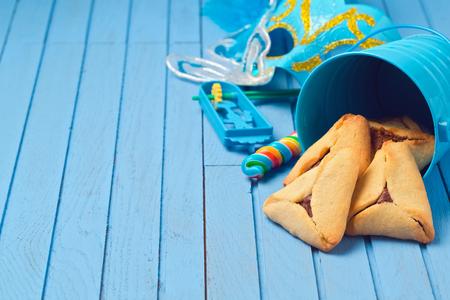 hamantaschen: Hamantaschen cookies in bucket for Purim holiday on blue wooden background