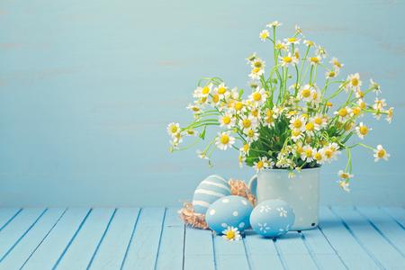 나무 파란색 테이블에 데이지 꽃과 페인트 계란 부활절 휴일 장식 스톡 콘텐츠