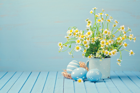 Easter holiday decoration with daisy flowers and painted eggs on wooden blue table