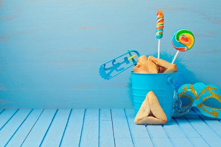 jewish background: Purim traditional gifts with hamantaschen cookies, noisemaker and carnival mask on blue background Stock Photo