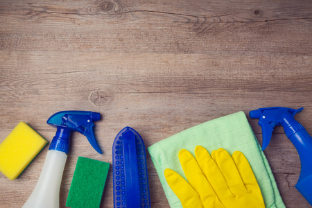 household equipment: Cleaning concept with supplies on wooden background. View from above
