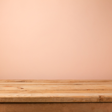 Empty wooden deck table over creamy wallpaper background