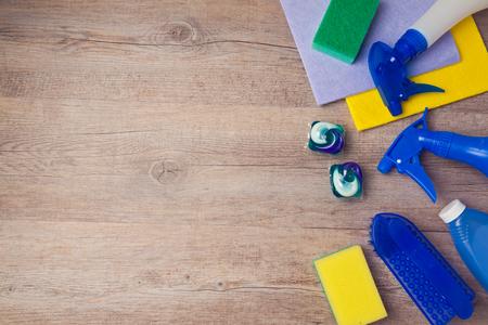 La limpieza y el trabajo doméstico concepto con los suministros en el fondo de madera. Vista desde arriba, con copia espacio