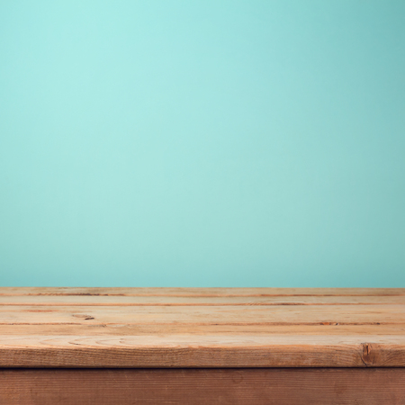 table: Empty wooden deck table over mint wallpaper background