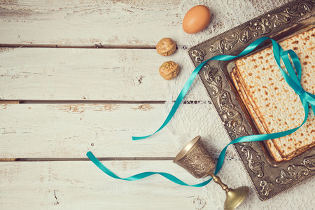 Jewish holiday Passover background with matzoh on wooden white table. View from above. Standard-Bild