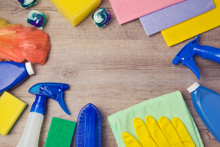 Cleaning and household concept with supplies on wooden background. View from above