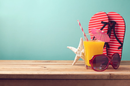flip flops on the beach: Summer holiday vacation background with orange juice and flip flops