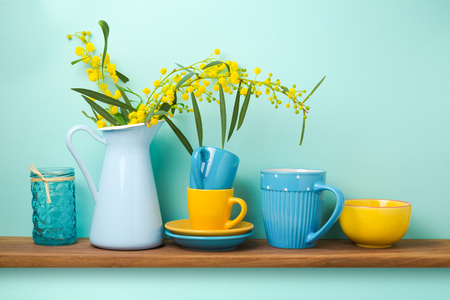Kitchen shelf with flowers in vase and tableware