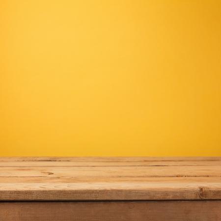 노란색 벽지 배경 위에 빈 나무 데크 테이블