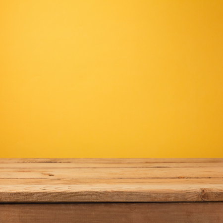 Empty wooden deck table over yellow wallpaper background Stockfoto