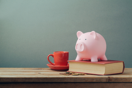 Piggy bank on wooden table with coffee cup and book. Saving money, budget planning concept.
