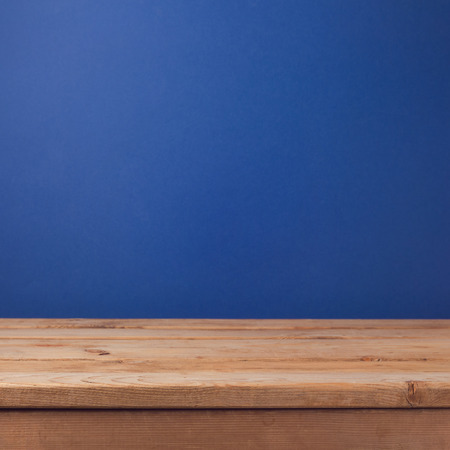solid background: Empty wooden deck table over dark blue wallpaper background