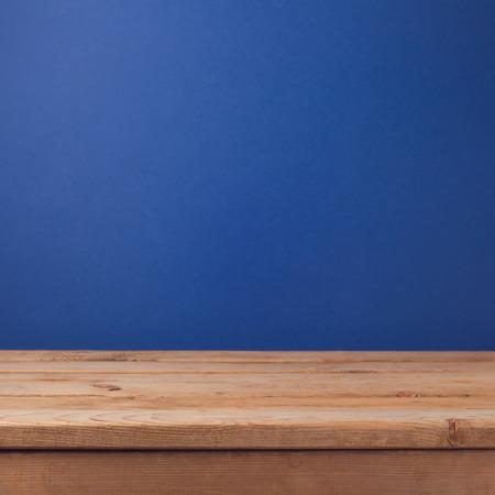 dark blue: Empty wooden deck table over dark blue wallpaper background