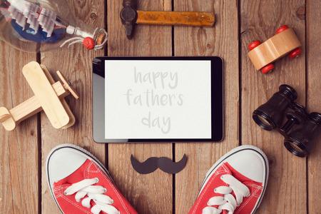 快乐的父亲节潮人背景与数字平板模拟模板。从上面的观点