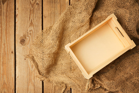 sack cloth: Wooden box on sack cloth on wooden background. View from above Stock Photo