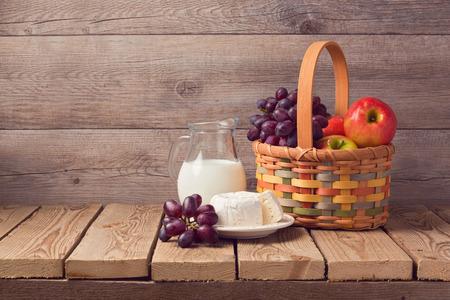 corbeille de fruits: Lait, fromage et panier de fruits sur la table rustique en bois. fête juive de Chavouot célébration