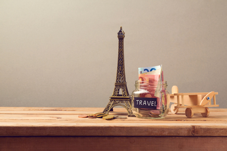 Travel to Paris, France concept with Eiffel Tower souvenir and wooden airplane toy. Planning summer vacation, money budget trip concept.