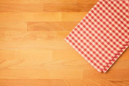 checked: Checked tablecloth on wooden kitchen counter. View from above Stock Photo