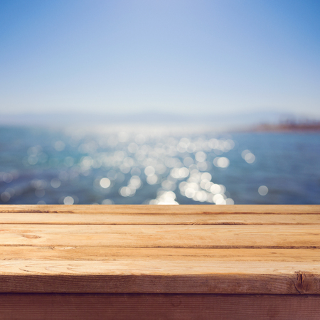 holiday table: Empty wooden deck table over sea bokeh background. Summer holiday vacation background.