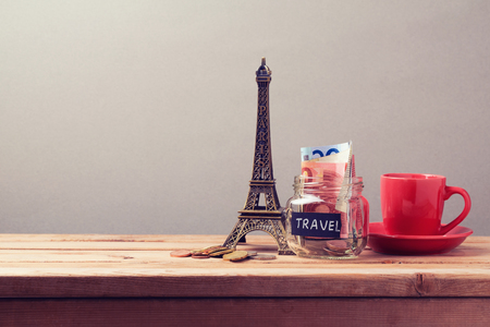 souvenir: Eiffel Tower souvenir and money box on wooden table. Planning summer vacation, money budget trip concept.