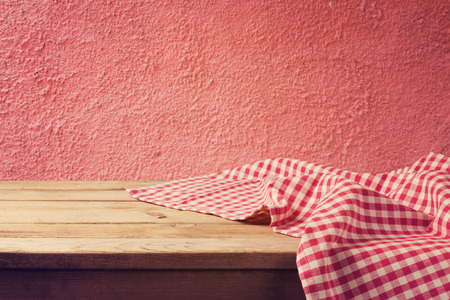mediterranian: Empty wooden deck table with red checked tablecloth over red wall background